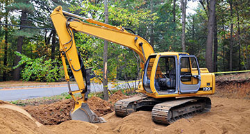 Mini excavator digging along side a residential road | Underground Utilities