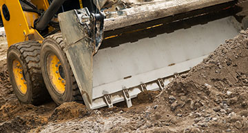 Close up of a skidloader bucket moving aggregate material | Demolition