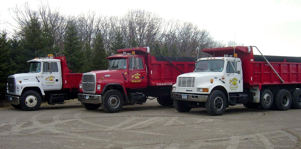 Row of three red and white South Side Sand & Gravel Dump Trucks